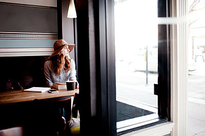 Thoughtful woman with coffee and books looking through window in cafe - p1166m1403729 by Cavan Images