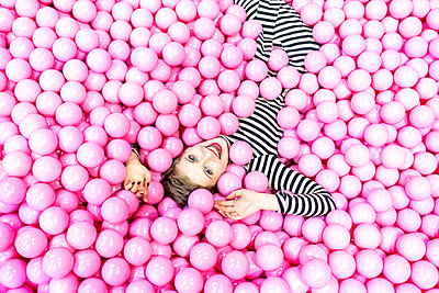Woman lying in ball pool - p1332m2055030 by Tamboly