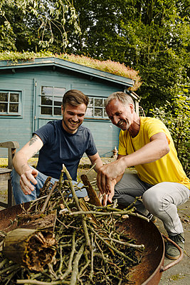 Happy father holding firewood while crouching by son in back yard - p300m2276953 by Gustafsson