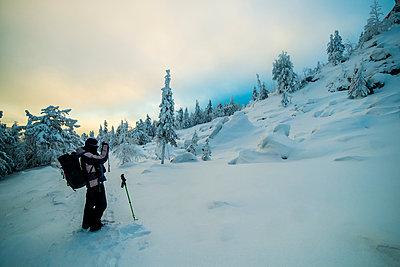 Caucasian man photographing snowy mountain - p555m1231748 by Aleksander Rubtsov