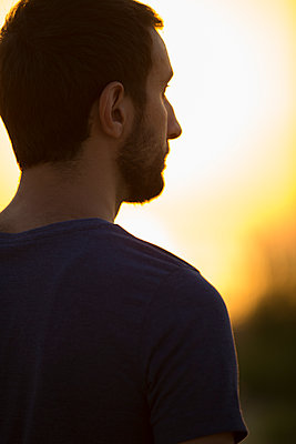 Young man looking away at sunset  - p794m1476425 by Mohamad Itani