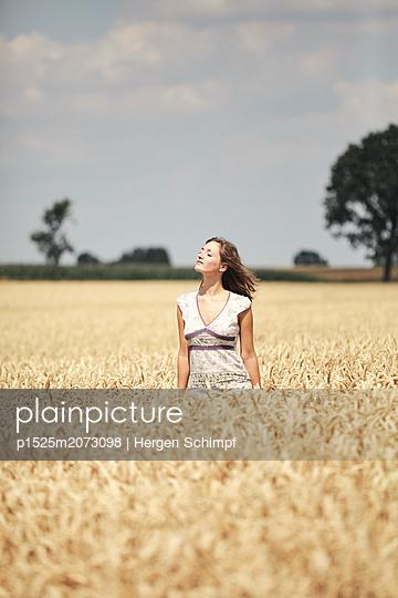 Mädchen sonnt sich in einem Kornfeld - p1525m2073098 von Hergen Schimpf