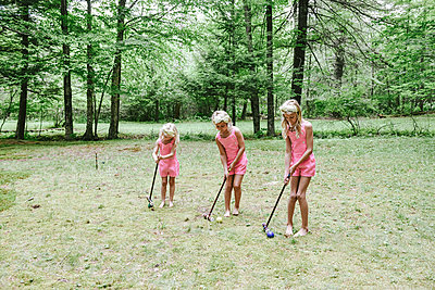 Three girls playing croquet - p1086m2149978 by Carrie Marie Burr