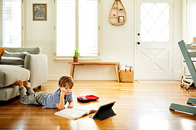 Boy lying on hardwood floor while studying in living room at home - p1166m2285858 by Cavan Images