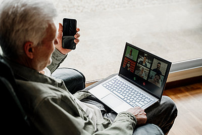 Senior man with mobile phone talking on video call through laptop at home - p300m2281372 by VITTA GALLERY