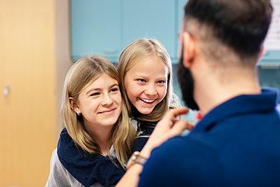 Smiling girls talking with teacher - p312m2174459 by Scandinav