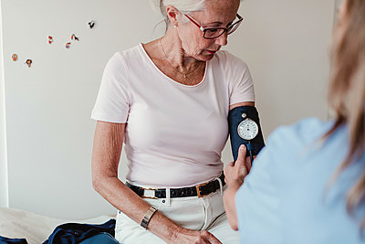 Female doctor checking blood pressure of senior woman in hospital - p426m2135486 by Maskot