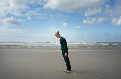 Boy standing on beach,leaning forward in the stormy wind, Gravelines, Nord-Pas-de-Calais, France - p429m1494183 by Mischa Keijser
