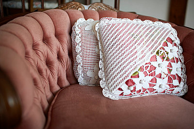 Two ornate pillows on a vintage retro chair - p5350197 by Michelle Gibson