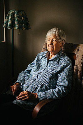 Older mixed race woman sitting in armchair - p555m1408715 by Shestock