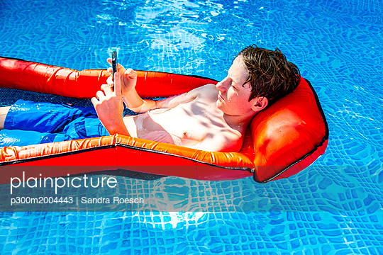 Boy floating on water in swimming pool using smartphone - p300m2004443 von Sandra Roesch
