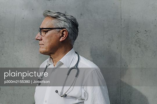 Pensive senior doctor at a concrete wall - p300m2155380 by Joseffson