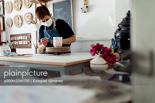Small business owner painting cup in her crafts workshop - p300m2240703 by Ezequiel Giménez