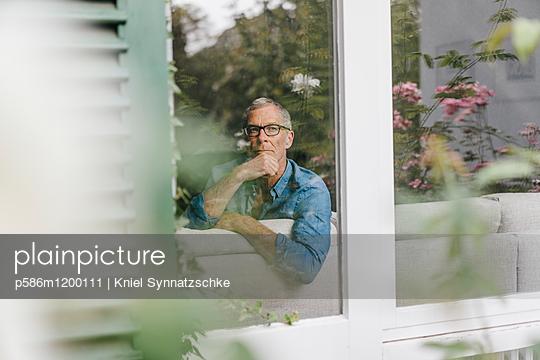 Reifer Mann blickt aus dem Fenster - p586m1200111 von Kniel Synnatzschke