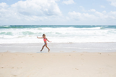 Playful girl running at beach against cloudy sky - p1166m1404029 by Cavan Images