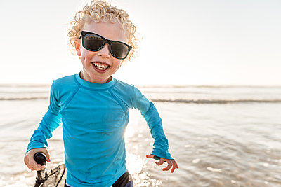 Portrait of curly haired happy boy with dimples and sunglasses - p1166m2108117 by Cavan Images