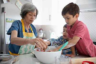 Grandmother and grandsons baking in kitchen - p1192m2109875 by Hero Images