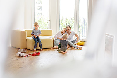 Happy family with two sons playing in living room of their new home - p300m2121760 by Peter Scholl