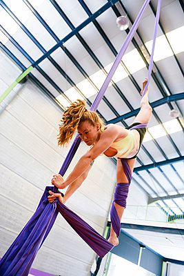 Young woman doing aerial silk in an exercise room - p300m2140168 by Javier Sánchez Mingorance