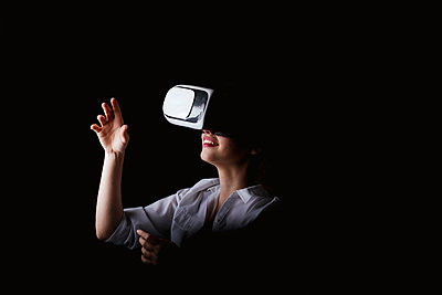 Young woman using VR glasses against black background - p300m2199233 by DREAMSTOCK1982