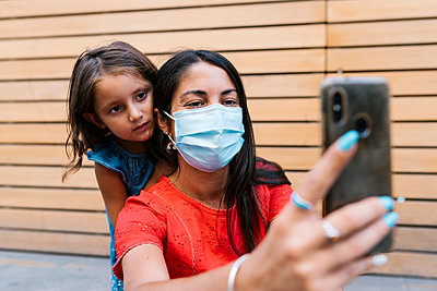 Mother wearing mask taking selfie with daughter against wall - p300m2220681 by Ezequiel Giménez