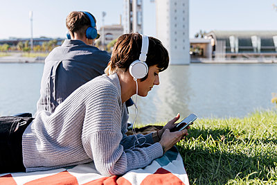 two women chilling and listening music on headphone in the riverside - p300m2253008 von Julio Rodriguez