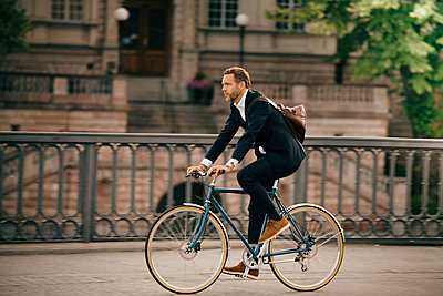 Full length of businessman cycling on street in city - p426m2145631 by Maskot