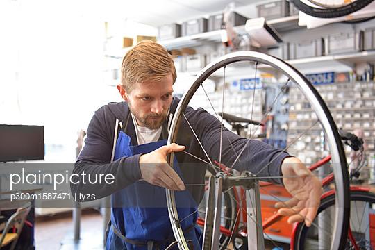 Bicycle mechanic in his repair shop, portrait - p300m1587471 von lyzs
