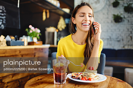 Smiling young female eating berry while talking on smart phone at table in cafe - p300m2225200 by Bartek Szewczyk