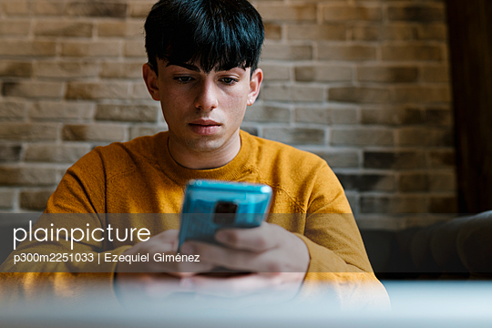 Young man using mobile phone while sitting at cafe - p300m2251033 by Ezequiel Giménez