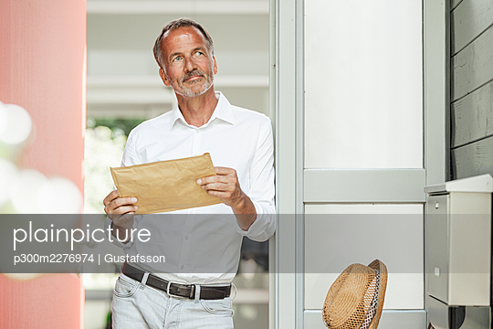 Mature man with parcel looking away while leaning on doorway - p300m2276974 by Gustafsson
