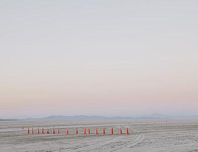 Row of traffic cones on the flat desert surface of  Black Rock, Nevada. - p1100m876520f by Paul Edmondson