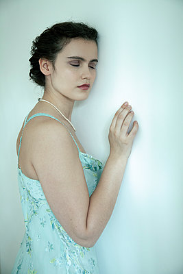 Woman with pearl necklace in strap dress leaning against wall - p1248m2270287 by miguel sobreira