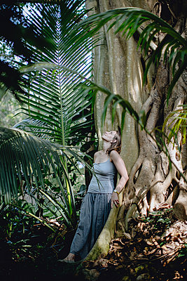 Woman leaning on big tree in tropical forest - p1414m1590570 by Dasha Pears