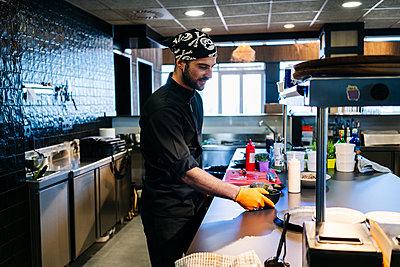 Chef preparing a dish in restaurant kitchen - p300m2166734 by Daniel González