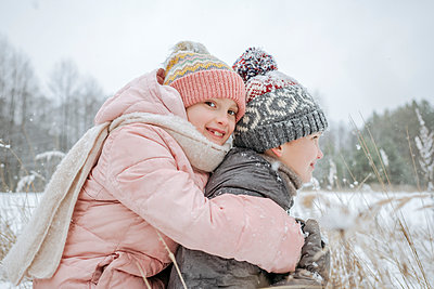 Boy giving his little sister a piggyback ride in winter forest - p300m2166998 by Ekaterina Yakunina