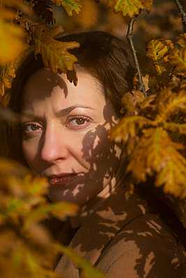 Woman hiding between autumn leaves  - p794m2141723 by Mohamad Itani