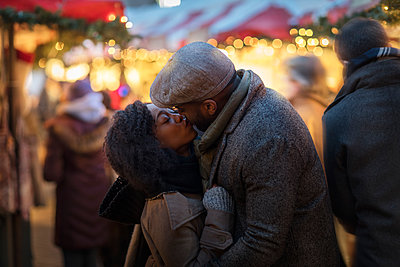 Romantic couple kissing at Christmas market, New York, USA - p924m1230233 by Steve Prezant