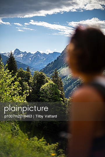 Woman looking at Aravis mountain range, Alps, France - p1007m2216463 by Tilby Vattard