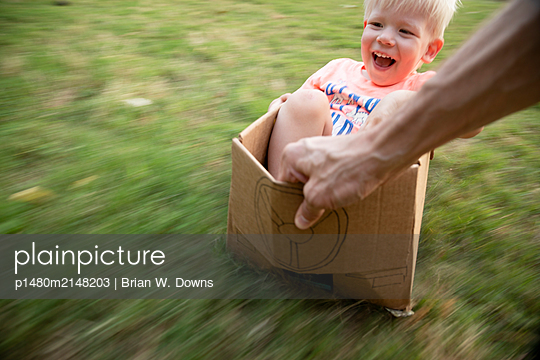 A father pulls his excited son in a cardboard car across their backyard