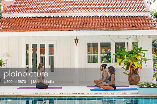 Two women and a man practicing yoga at the poolside - p300m1587011 von Mosu Media