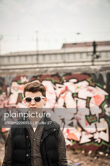 Portrait of a teenage boy wearing sunglasses in an old run down industrial area - p300m2206553 by Studio 27