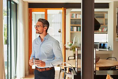 Thoughtful businessman drinking coffee at home - p1023m2196677 by Paul Bradbury