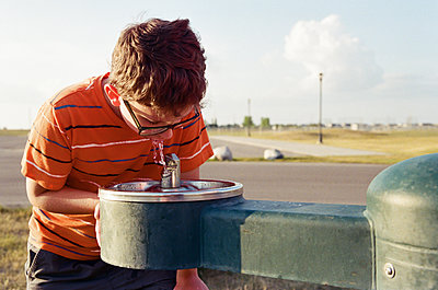 Boy drinking water from fountain at park - p1166m1542557 by Cavan Social