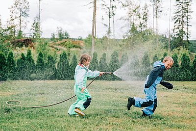 sister spraying her brother with a hose whilst playing in the rain - p1166m2201755 by Cavan Images
