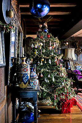 Christmas tree and blue baubles with vase display on side table in Cheltenham country home - p349m790920 by Polly Eltes
