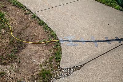 Elektrokabel mit Klebestreifen auf Betonweg befestigt  - p397m2013396 von Peter Glass