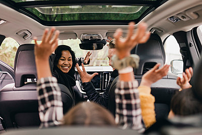 Cheerful family raising hands while enjoying road trip in electric car - p426m2194948 by Maskot