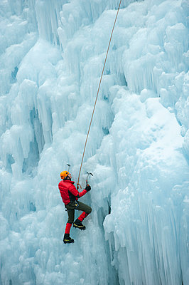 Caucasian man climbing ice wall - p555m1479335 by Pete Saloutos