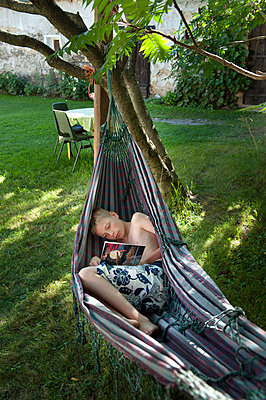 Lazing around in hammock - p896m834551 by Sabine Joosten